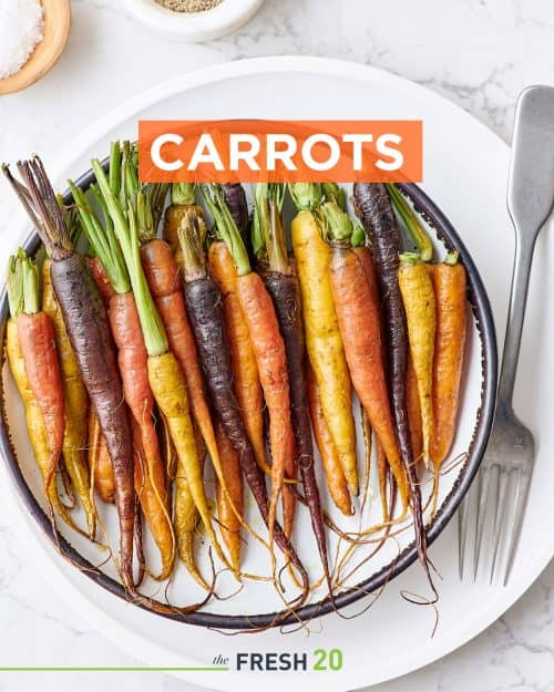 Colorful orange yellow and purple roasted carrots with their tops in a white ceramic bowl