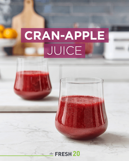 Two beautiful glasses filled with deep rich red cranberry apple juice in a white marble kitchen
