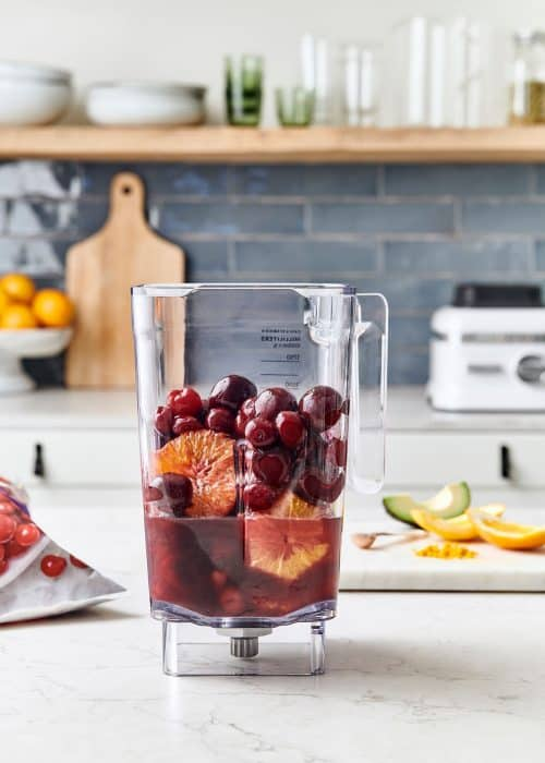 Blender full of pomegranate juice, oranges, cherries & avocado on a white marble surface in a beautiful kitchen