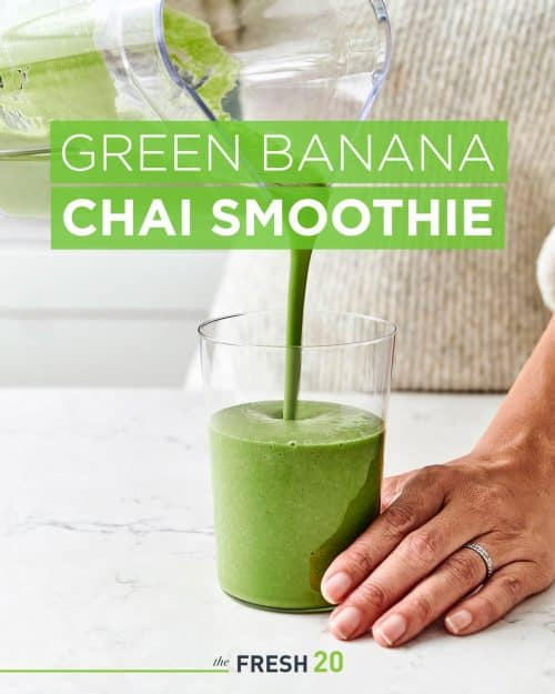 Woman pouring green banana chai spice superfood smoothie into a clear glass in a white marble kitchen