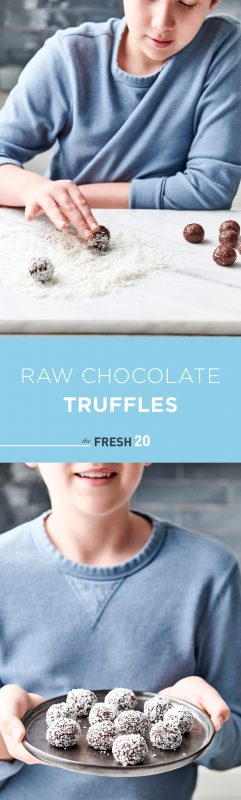 Young boy rolling heart healthy raw chocolate truffles in a pile of shredded coconut in a white marble kitchen