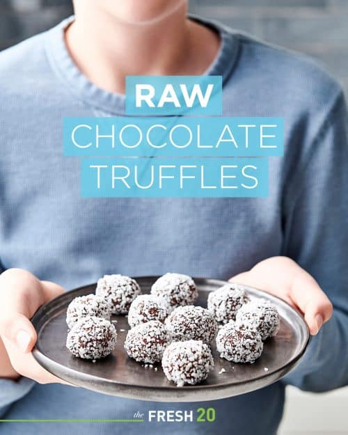 Young boy holding up a black ceramic platter of heart healthy raw chocolate truffles