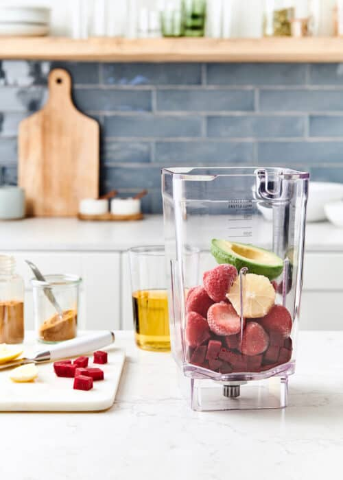 Blender full of beets, strawberries & avocado with ingredients on a wood cutting board in a white marble kitchen