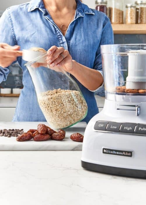 Woman scooping out oatmeal to make healthy cookies with a food processor in a modern kitchen
