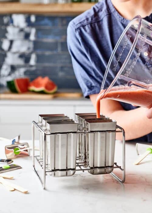 Pouring blended watermelon mint smoothie into metal popsicle forms
