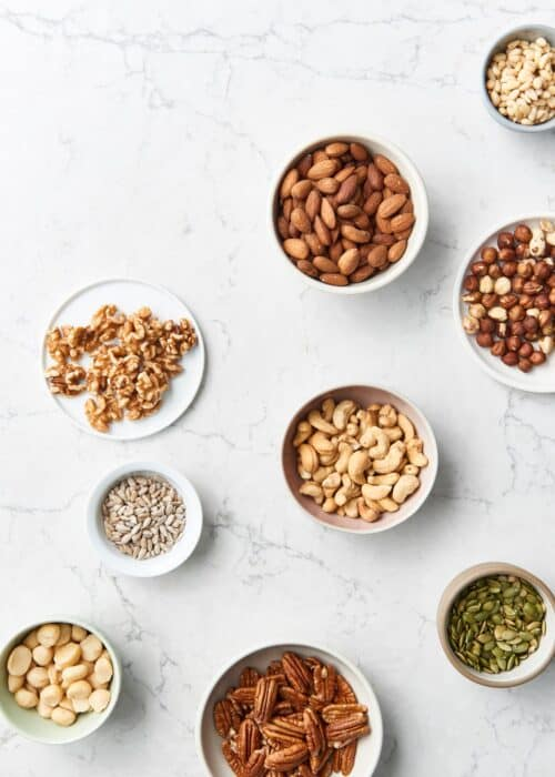Small bowls of healthy nuts & seeds on a marble counter