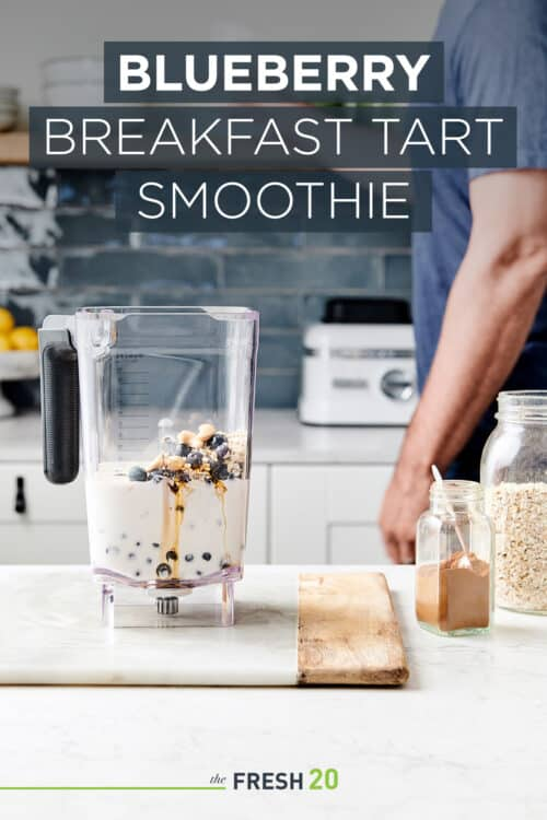 Man preparing a vegan smoothie in a blender full of creamy almond milk, honey, cinnamon and blueberries in a beautiful white marble kitchen
