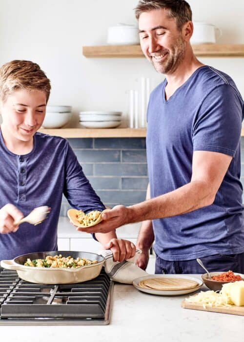 Father and son using tortillas to wrap burritos filled with egg mixture in a beautiful marble kitchen