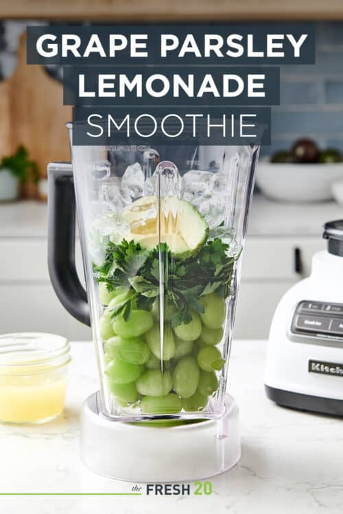 Vibrant healthy green grape parsley lemonade smoothie in a blender in a beautiful white marble modern kitchen