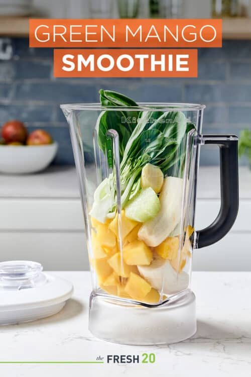 Blender full of fresh mango, bannanas, lime & bok choy in a beautiful white marble kitchen