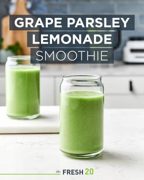 Two tall glasses of healthy green grape parsley lemonade smoothie in a beautiful white marble kitchen