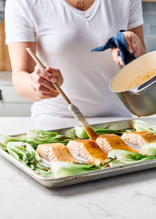 Woman glazing a sheet pan full of maple soy salmon and bok choy on a white marble surface