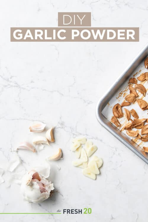 Baking sheet full of crispy baked garlic alongside raw chopped garlic cloves on a white marble surface
