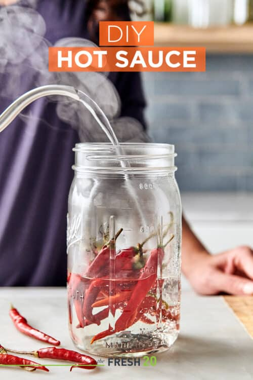 Woman pouring steaming boiling water from a kettle into a mason jar filled with deep red hot chili peppers