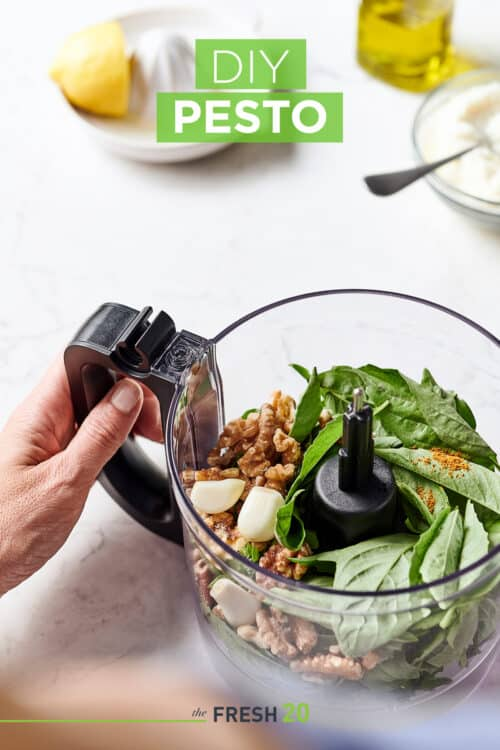 Food processor full of fresh basil, garlic and walnuts along with a lemon juicer & olive oil on a white marble surface