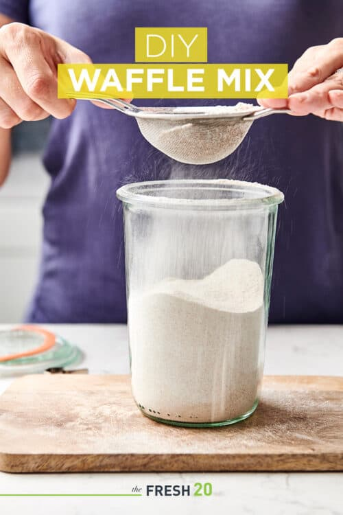 Woman sifting DIY easy decadent waffle mix into a Weck glass containter on a wooden cutting board