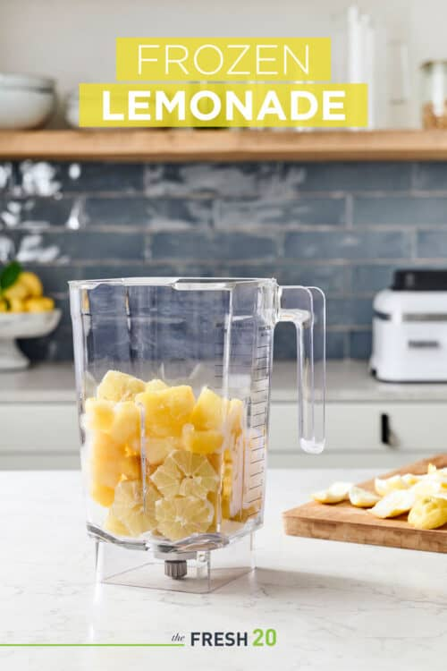 Blender full of yellow fruits such as lemons and pineapple in a beautiful marble kitchen