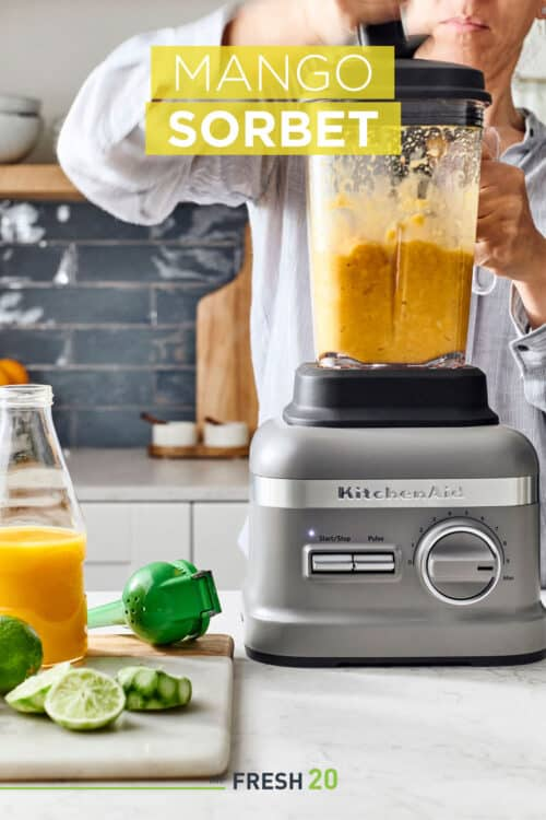Woman using KitchenAid blender filled with mangos, limes and orange juice in a white marble kitchen