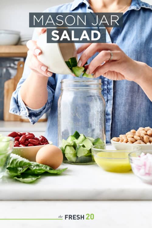 Woman filling glass mason jar with salad & bowls of vegetable ingredients in a white marble kitchen