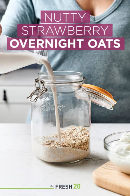 Woman pouring fresh almond milk into glass mason jar filled with oatmeal in a white marble kitchen
