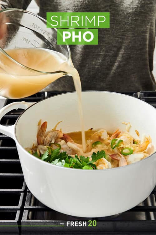 Pouring a rich resturant style broth into a Le Creuset Dutch oven filled with shrimp and other ingredients on a metal cooktop