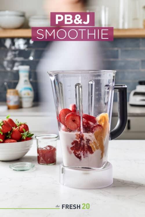 Blender full of almond milk, peanut butter, & a bowl of strawberries & jam in a white marble kitchen