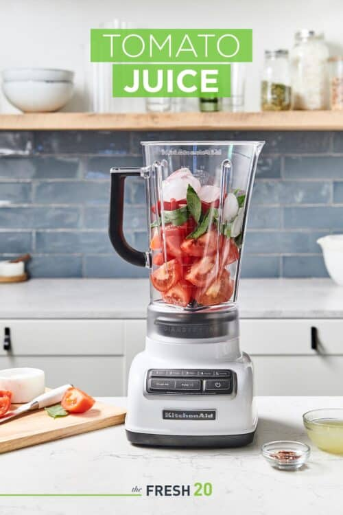 Blender full of tomatoes, basil & red bell peppers next to chopped ingredients on a wood cutting board in a white marble kitchen