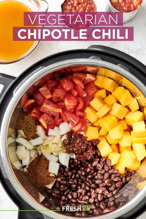 Vegetarian chipotle chilli fresh organized ingredients inside an Instant Pot Crock-Pot on a white marble surface from above
