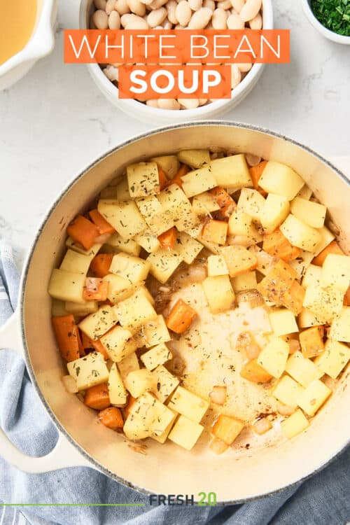 Le Cruset pot full of cubed potatoes and carrots alongside a bowl of white beans on a white marble surface