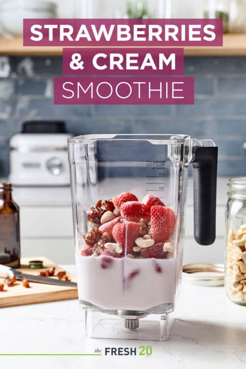 Blender full of strawberries, almond milk, nuts, dates & other ingredients on a wood cutting board in a white marble kitchen