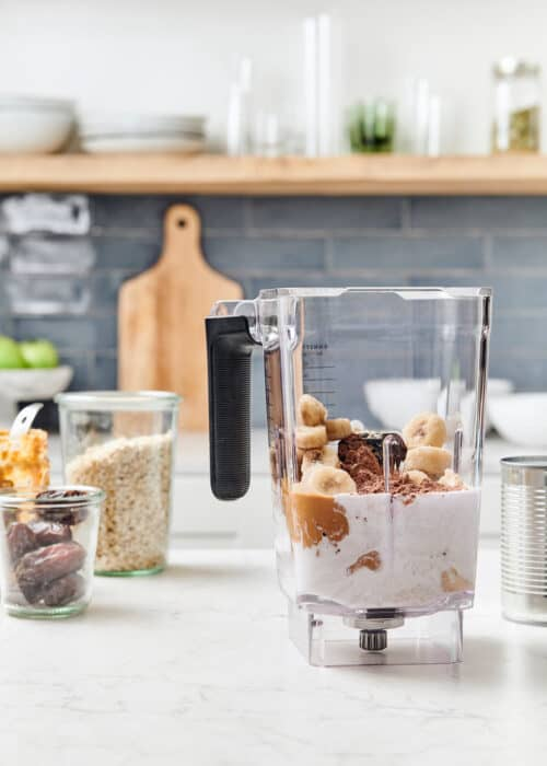 Cacao peanut butter & banana in a blender with mason jars full of dates and oats in a beautiful modern kitchen