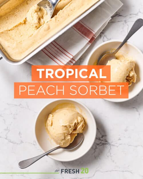2 bowls and a tray with scoops of homemade peach sorbet on a white marble surface