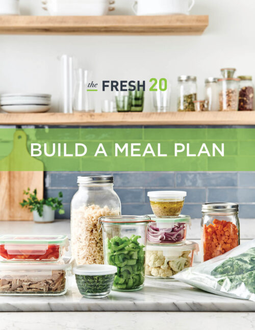 Healthy fresh produce in glass containers for meal prep in a warm white marble kitchen