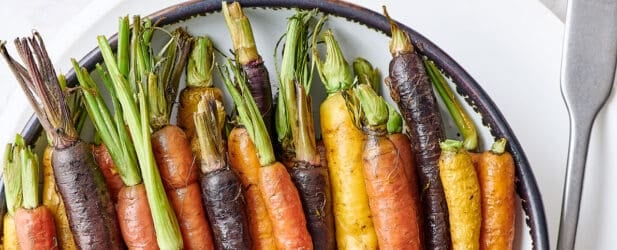 Colorful orange yellow and purple roasted carrots with their tops in a ceramic bowl